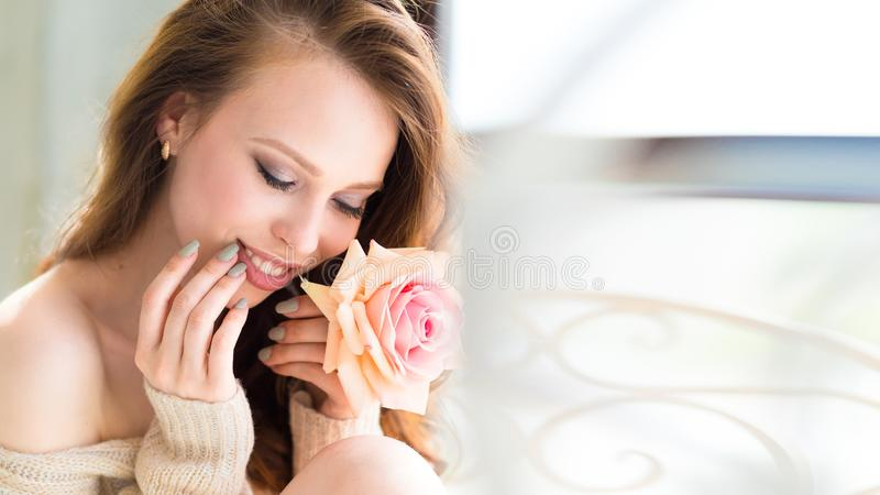 Jeune visage modèle de fille de beauté en gros plan avec la fleur rose près des lèvres Concept facial de traitement de soins de l photographie stock