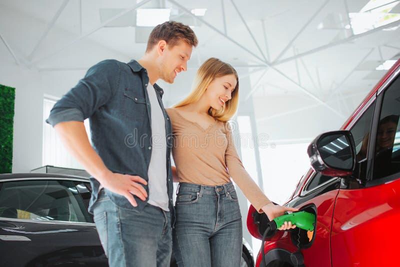 Jeune voiture électrique de achat de sourire de couples première dans la salle d'exposition Femme chargeant le véhicule qui respe images libres de droits