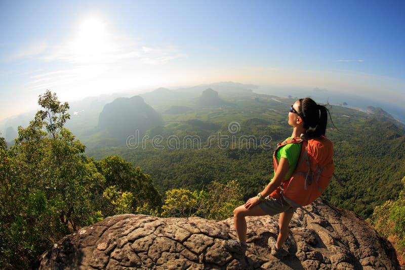 Jeune voyageur avec le sac à dos sur la roche de crête de montagne observant la localité photos libres de droits