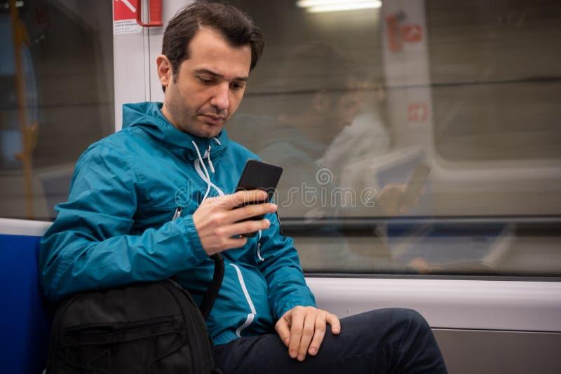 Jeune voyageur lisant le r?seau social au t?l?phone portable sur le transport en commun de m?tro de souterrain image stock