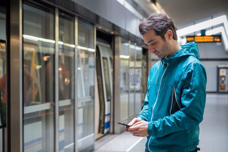 Jeune voyageur lisant le r?seau social au t?l?phone portable sur le transport en commun de m?tro de souterrain images stock