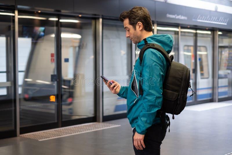 Jeune voyageur lisant le r?seau social au t?l?phone portable sur le transport en commun de m?tro de souterrain photo libre de droits