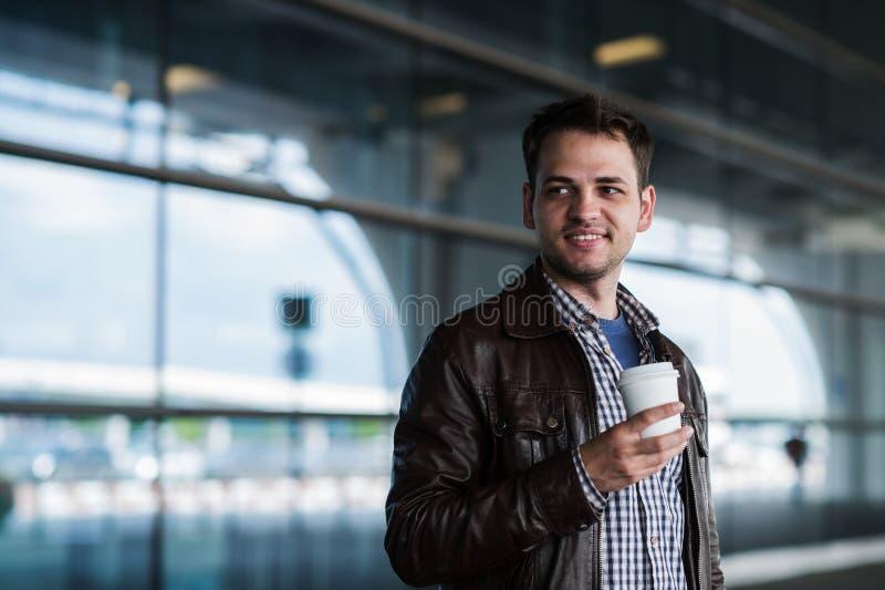 Jeune voyageur masculin beau élégant avec le poil se tenant dehors près du terminal d'aéroport Veste de port d'homme et images libres de droits