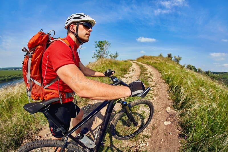 Jeune voyageur masculin montant un vélo de montagne sur un coucher du soleil photos libres de droits