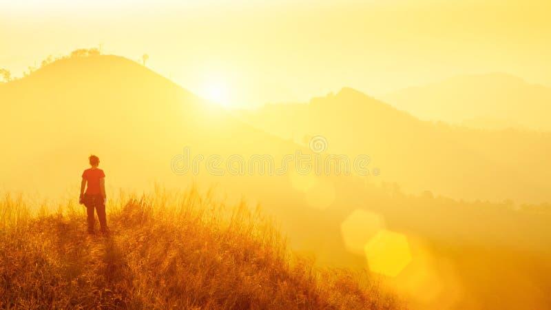 Jeune voyageur se tenant à la montagne au lever de soleil Voyage, vacatio photos libres de droits