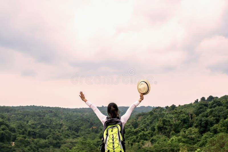 jeune voyageuse asiatique de femme avec le sac ? dos d?tendant sur la for?t mountian et regardante photo libre de droits