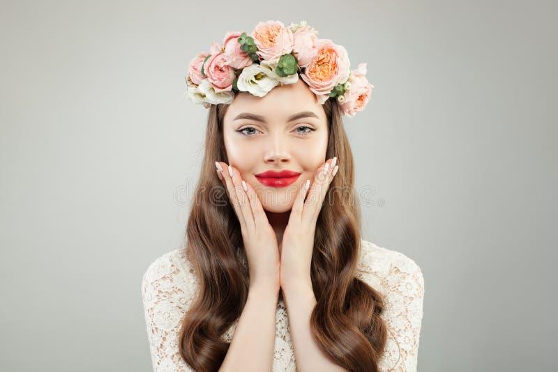 Jeune Woman modèle de sourire avec la peau claire, les cheveux bouclés de Brown, le maquillage, la manucure et les fleurs sur sa  photos stock