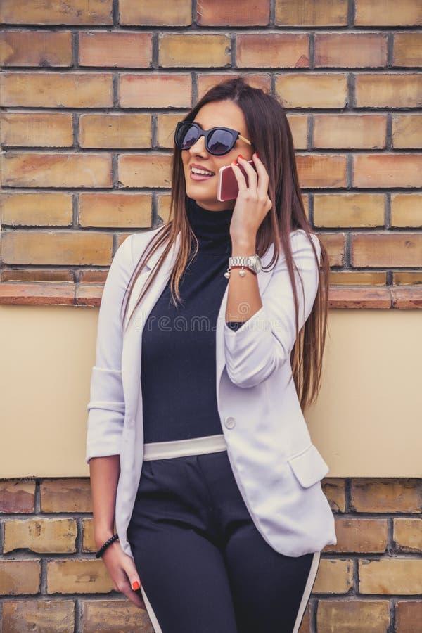 Jeune womanl heureux avec des lunettes de soleil riant tout en parlant sur la foule image stock