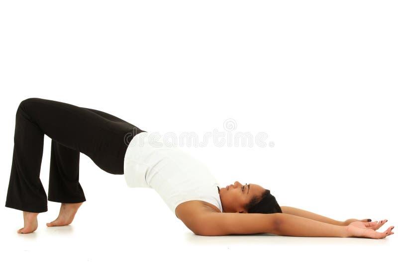 Jeune yoga de femme de couleur au-dessus du fond blanc photographie stock libre de droits