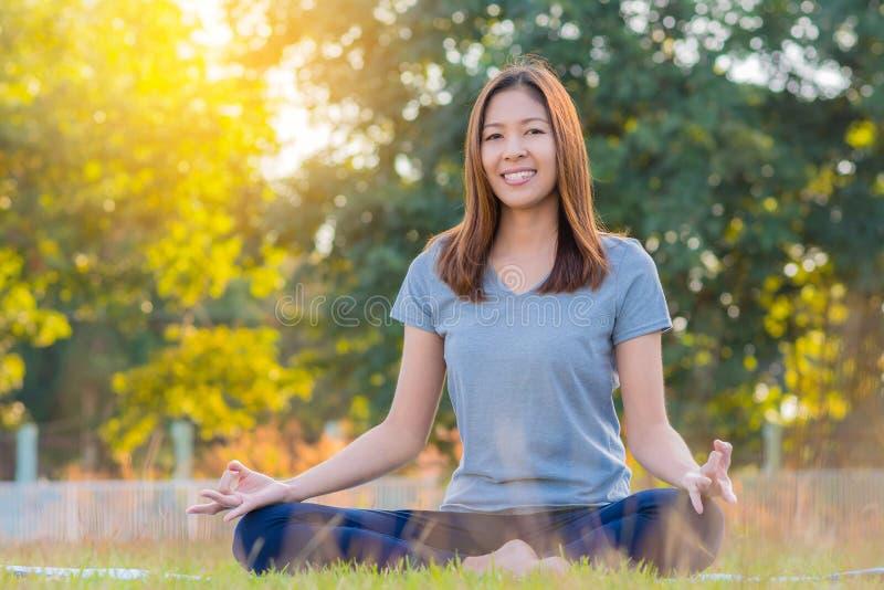 Jeune yoga de pratique de sourire asiatique de femme, se reposant dans la pose facile photo stock