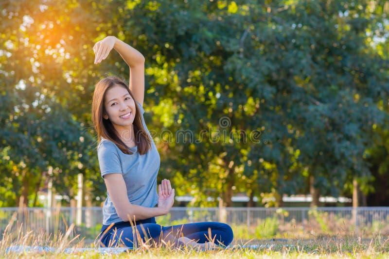 Jeune yoga de pratique de sourire asiatique de femme, se reposant dans la pose facile photos stock