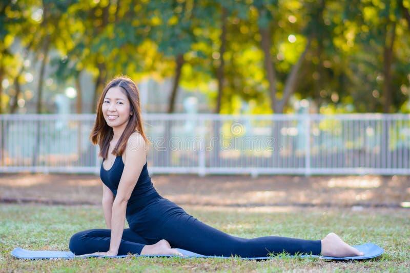 Jeune yoga de pratique de sourire asiatique de femme, se reposant dans la pose facile photographie stock