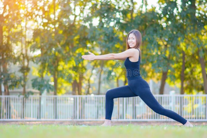 Jeune yoga de pratique de sourire asiatique de femme, se tenant dans la pose facile photos stock