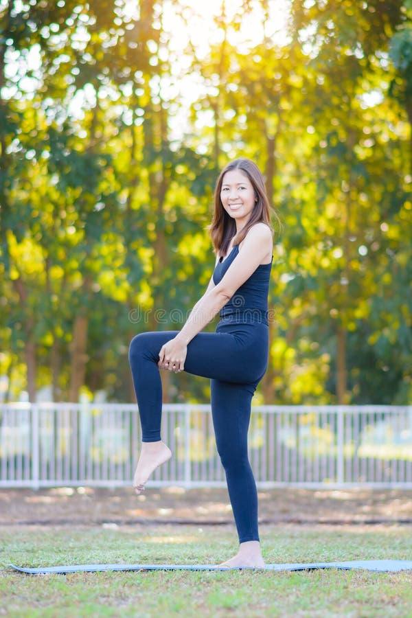 Jeune yoga de pratique de sourire asiatique de femme, se tenant dans la pose facile photos libres de droits