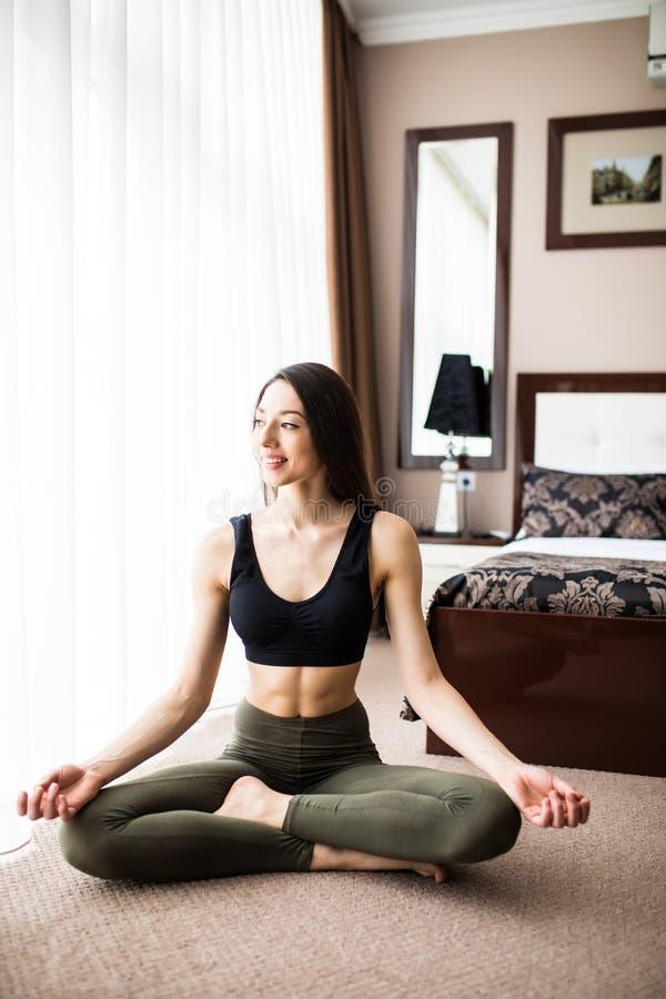 Jeune yoga de pratique de sourire attrayant de femme, presque se reposant dans le demi exercice de Lotus, pose d'Ardha Padmasana, photos libres de droits