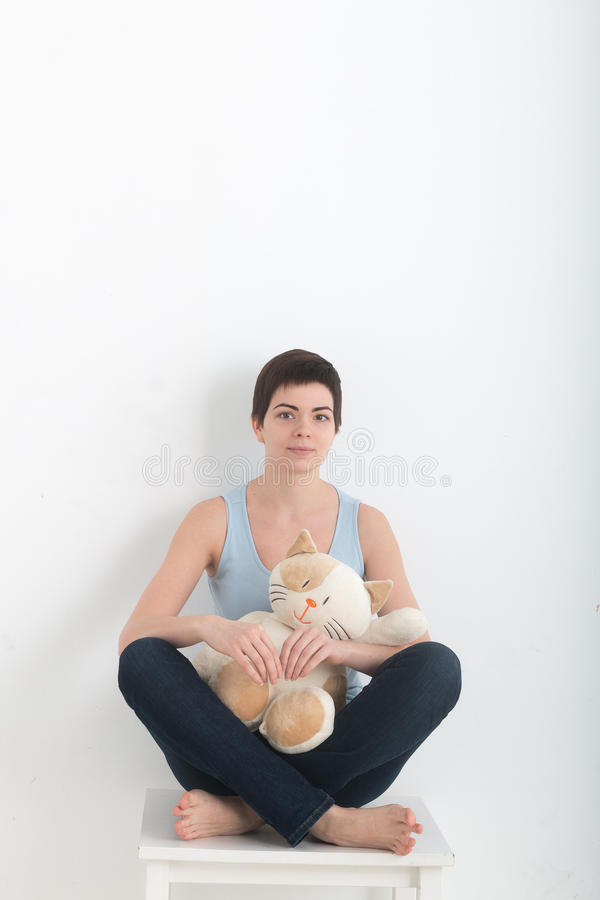 Jeune yoga de pratique de sourire attrayant de femme, se reposant dans la demi pose d'Ardha Padmasana d'exercice de Lotus, établi image libre de droits