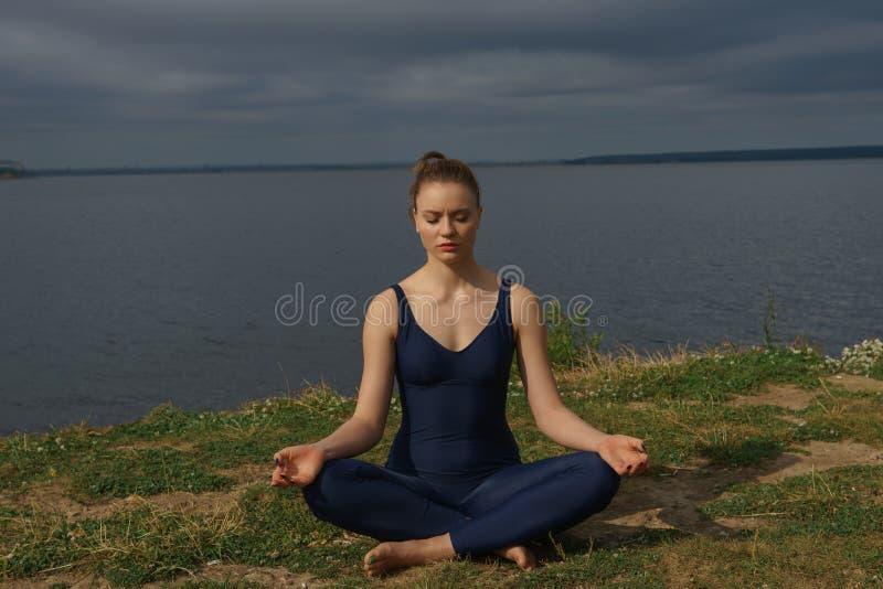 Jeune yoga de pratique de sourire attrayant de femme, se reposant dans le demi exercice de Lotus, pose d'Ardha Padmasana photographie stock