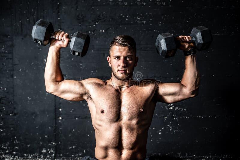 Jeunes épaules transpirantes et transpirantes entraînantes avec deux cloches dans la salle de gym image sombre avec ombres image libre de droits