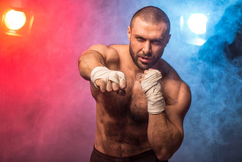 Jeunes éruptions de boxe musculaires de formation de combattant Kickboxer faisant un exercice de combat photographie stock