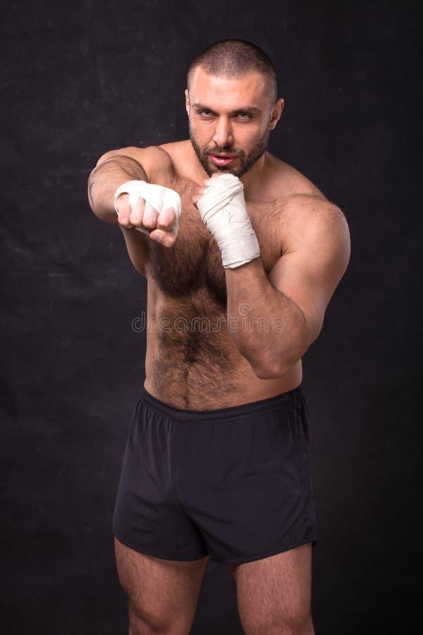 Jeunes éruptions de boxe musculaires de formation de combattant Kickboxer faisant un exercice de combat photos stock