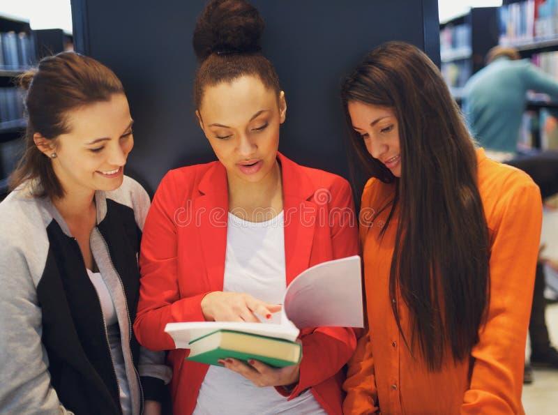 Jeunes étudiantes partageant un livre dans la bibliothèque photos stock