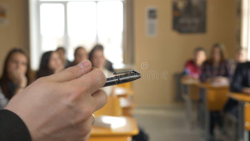 Jeunes étudiants écoutant la conférence avec l'intérêt sur l'université Plan rapproché de jeune main du ` s de professeur Les étu images stock