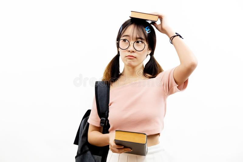 Jeunes étudiants de l'adolescence scolaires féminins asiatiques avec les verres à la mode d'oeil tenant la pile des livres avec l photographie stock