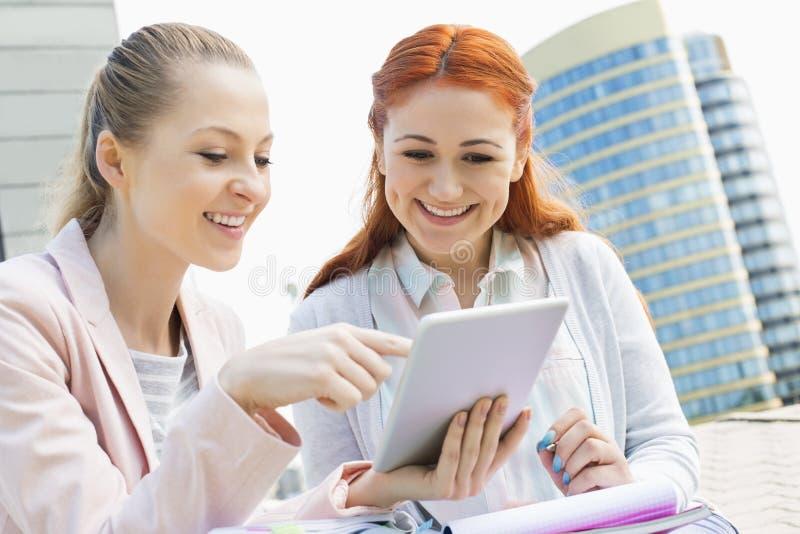 Jeunes étudiants de sourire à l'aide du comprimé numérique contre le bâtiment image stock