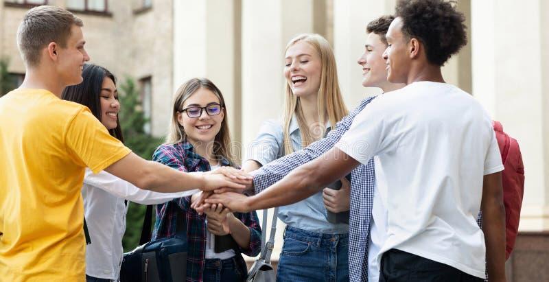 Jeunes étudiants empilant des mains ensemble dans le campus d'université image stock