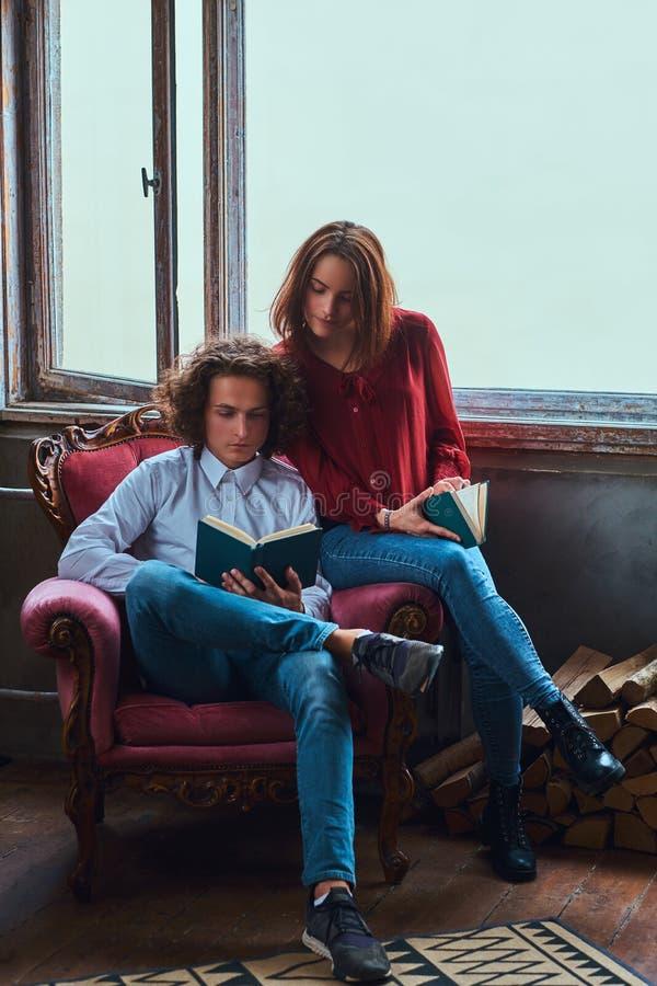 Jeunes étudiants lisant ensemble et s'asseyant sur une chaise images libres de droits