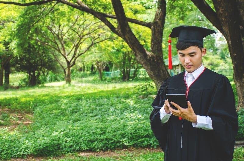 Jeunes étudiants masculins habillés dans la robe noire d'obtention du diplôme Nature comme fond Sourire de garçon gaiement, regar image stock