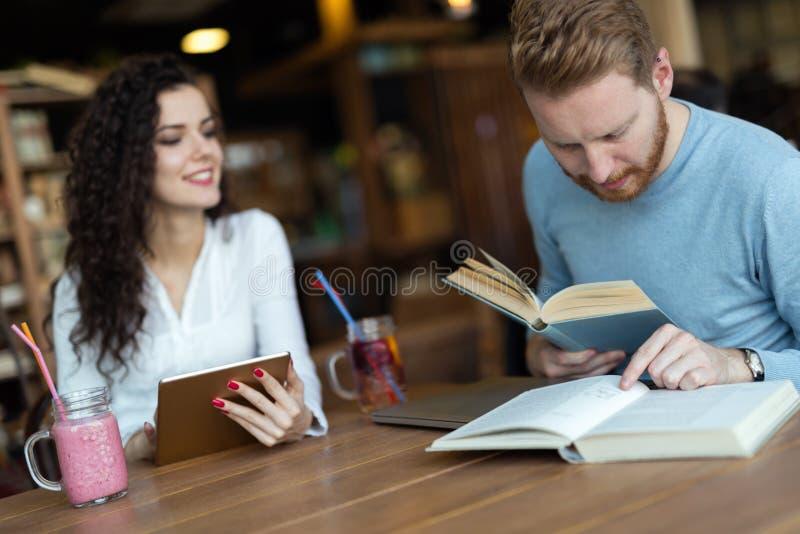 Jeunes étudiants passant le temps dans des livres de lecture de café photo libre de droits