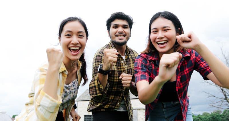 Jeunes étudiants réussis au campus regardant la caméra et le sourire et à hauts cinq tout en sautant sur l'extérieur photos libres de droits