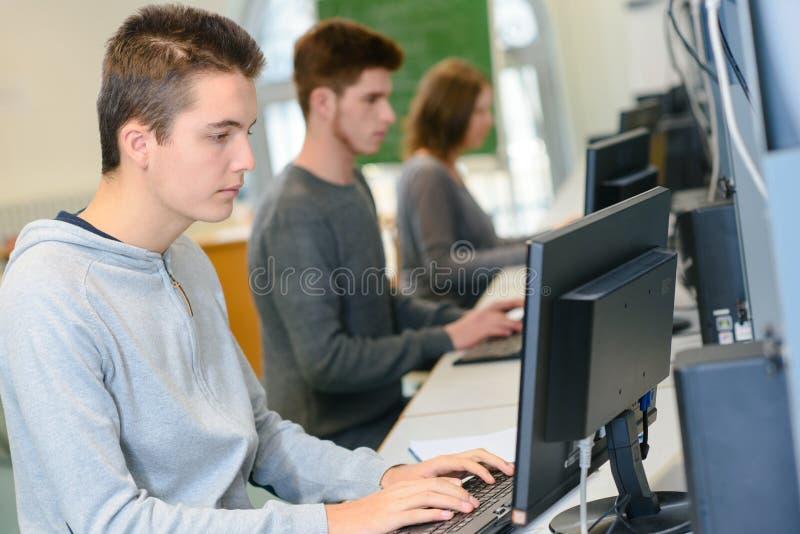 Jeunes étudiants tirés s'asseyant dans la salle des ordinateurs photo stock