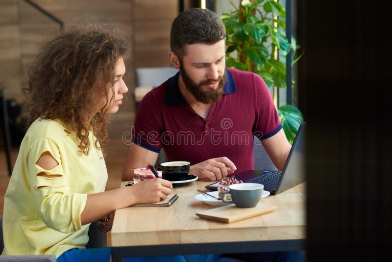 Jeunes étudiants travaillant utilisant l'ordinateur portable, fonctionnant dans le restaurant photo libre de droits