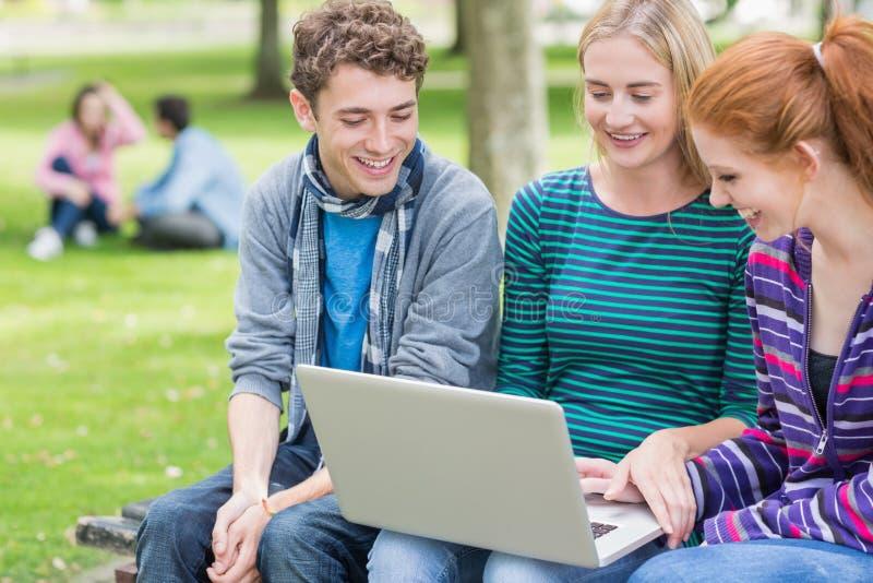 Jeunes étudiants universitaires à l'aide de l'ordinateur portable dans le parc photos stock