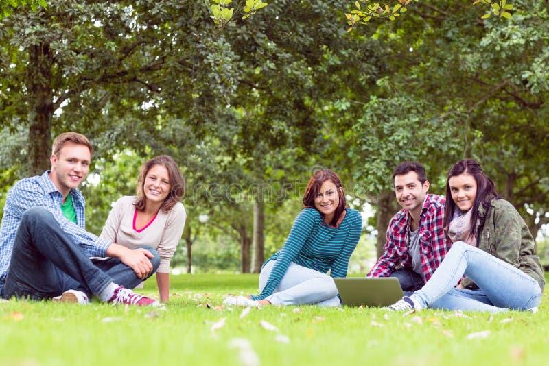 Jeunes étudiants universitaires à l'aide de l'ordinateur portable dans le parc photo stock