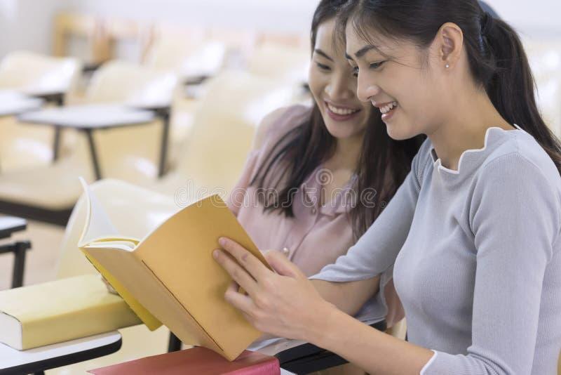 Jeunes étudiants universitaires lisant un livre ensemble dans la classe Educati images libres de droits