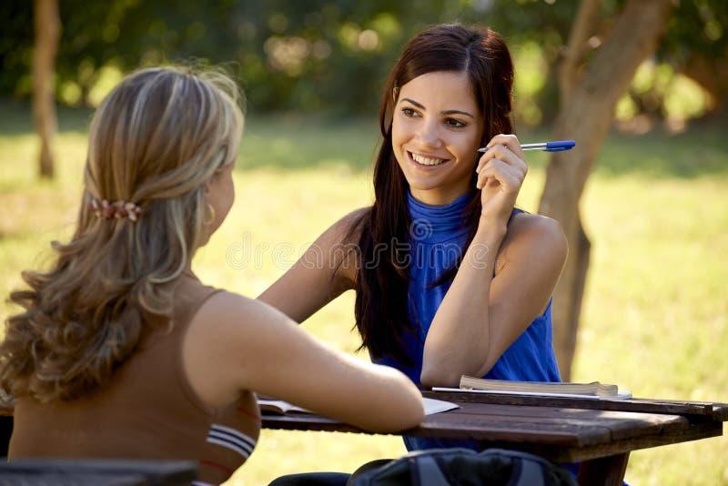 Jeunes étudiants universitaires parlant et étudiant pour l'examen d'université image stock