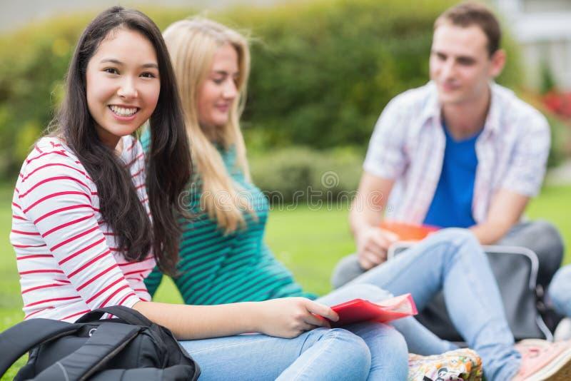 Jeunes étudiants universitaires s'asseyant en parc image stock
