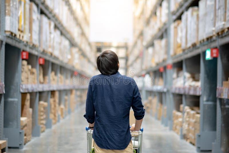 Jeunes achats asiatiques d'homme avec le chariot de chariot dans l'entrepôt photographie stock libre de droits