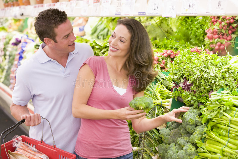 Jeunes achats de couples pour le produit frais photographie stock libre de droits