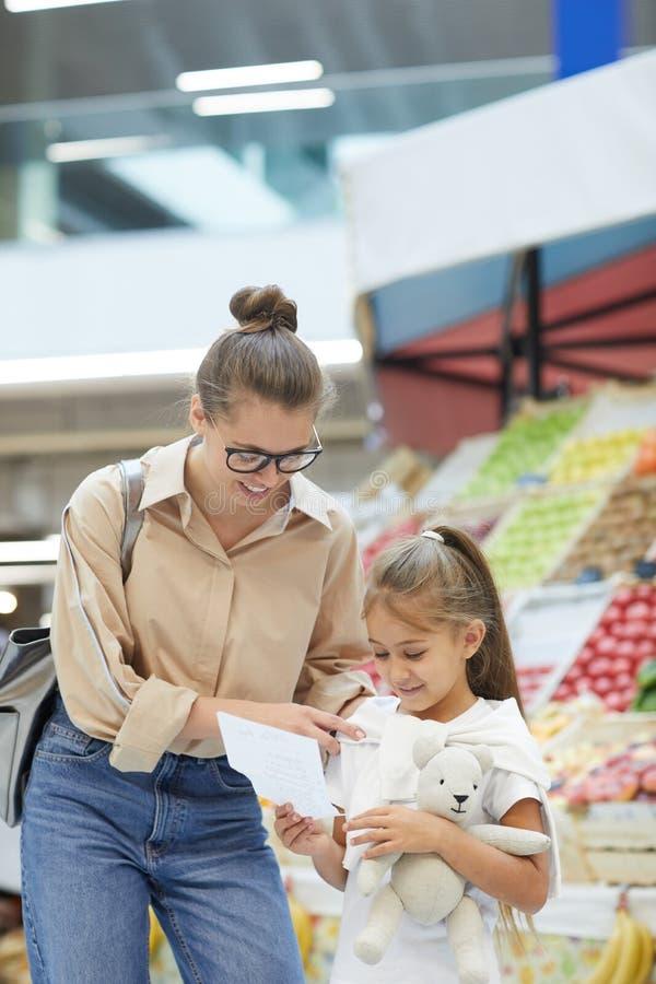 Jeunes achats de mère sur le marché d'agriculteurs photos stock