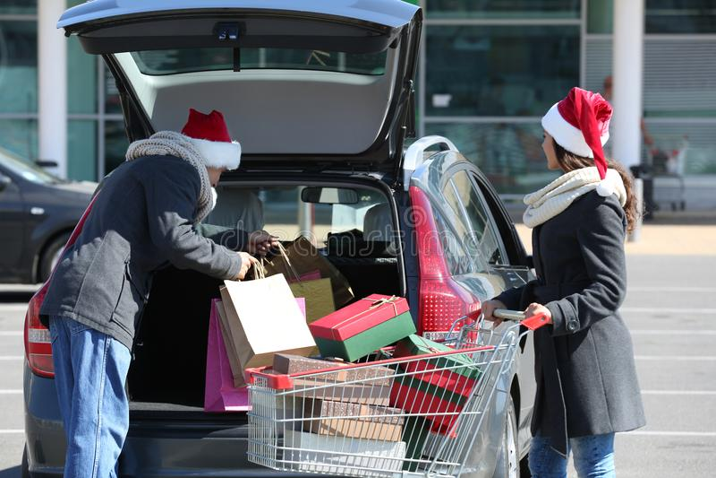Jeunes achats de Noël de chargement de couples dans le tronc de voiture sur le stationnement de centre commercial photos stock