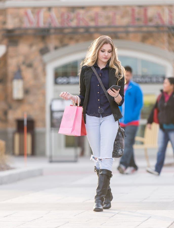 Jeunes achats femelles blonds avec les sacs roses et rouges tenant un téléphone portable photographie stock