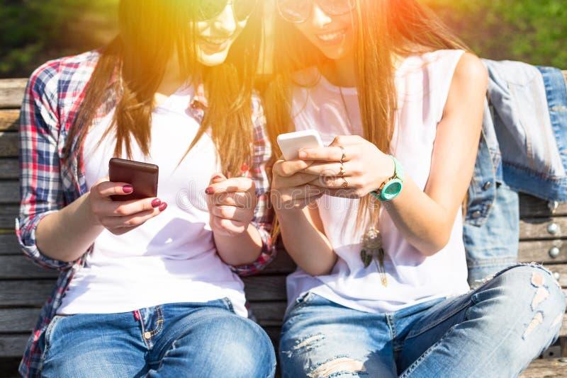Jeunes adolescentes heureuses à l'aide de leurs téléphones et ayant l'amusement dans le parc d'été photo libre de droits