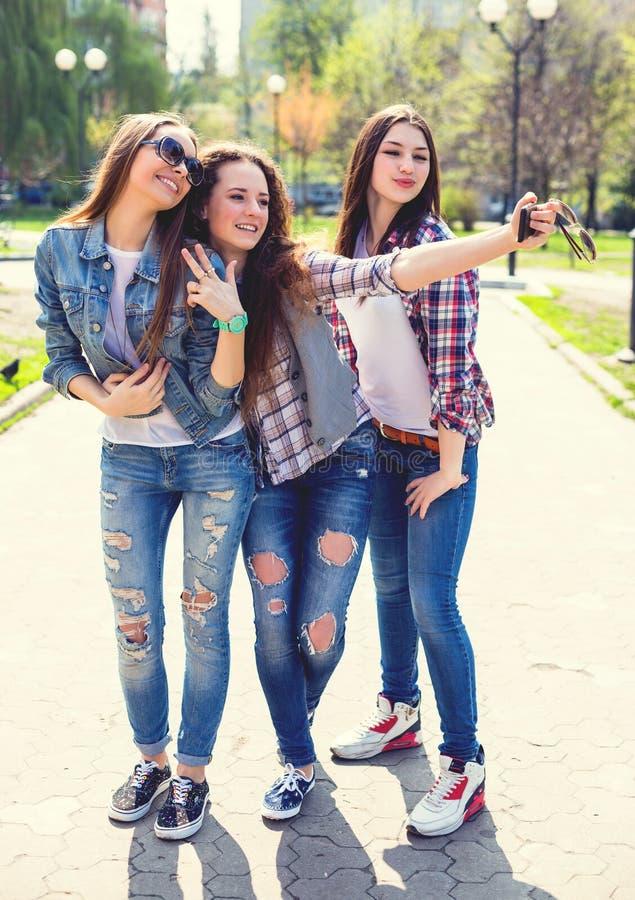 Jeunes adolescentes heureuses faisant le selfie et ayant l'amusement en parc d'été photographie stock libre de droits
