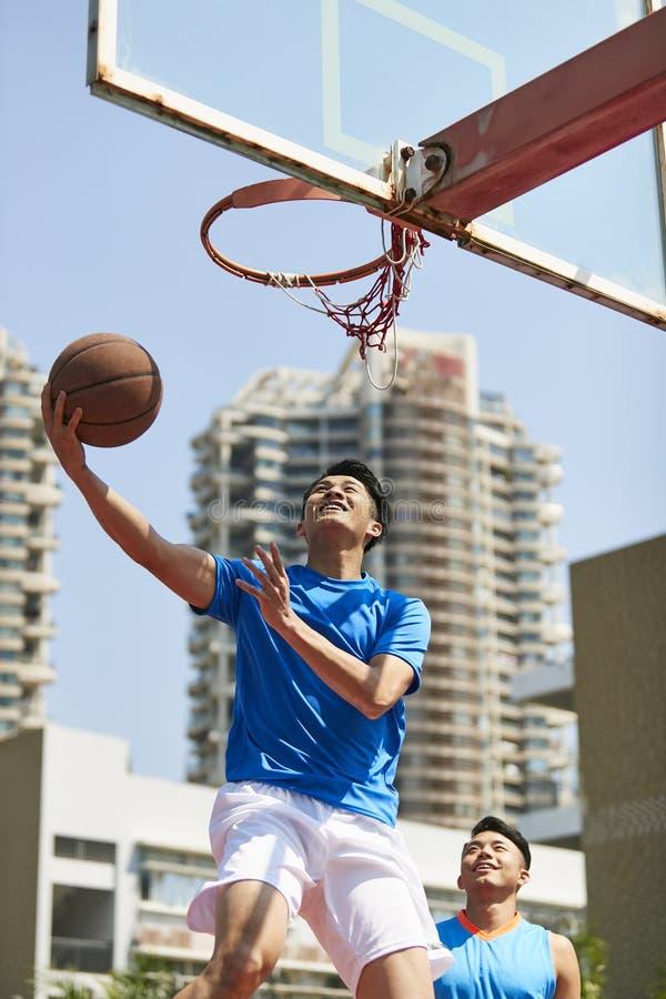 Jeunes adultes asiatiques jouant le basket-ball photo stock