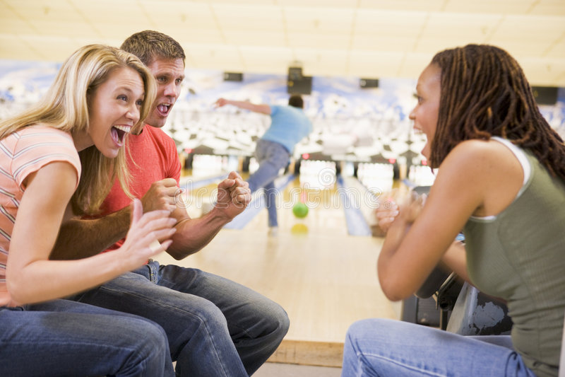 Jeunes adultes encourageant dans une ruelle de bowling photographie stock libre de droits