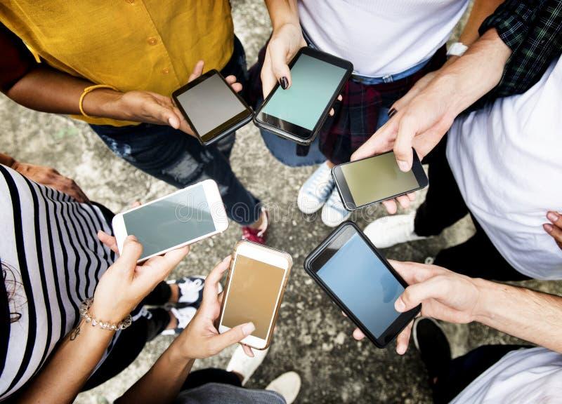 Jeunes adultes utilisant des smartphones dans le media d'un cercle et les conn. sociaux photographie stock libre de droits